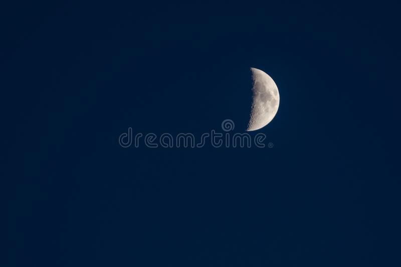 Details of a crescent moon on a clear blue sky royalty free stock image