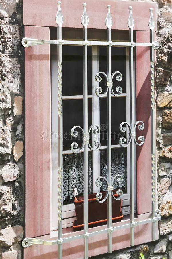 Details of the decor and interior. A fake window with a metal decorative grille on the facade of the building against the royalty free stock image