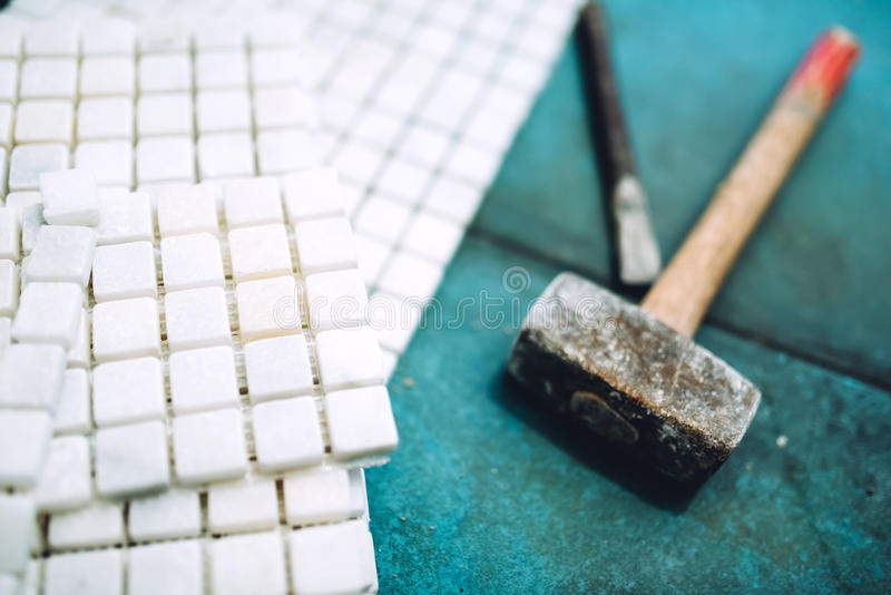 Details der Bauwerkzeug-, -badezimmer- und -küchenerneuerung - Stücke von Mosaikkeramikfliesen und von Gummihammer lizenzfreies stockfoto