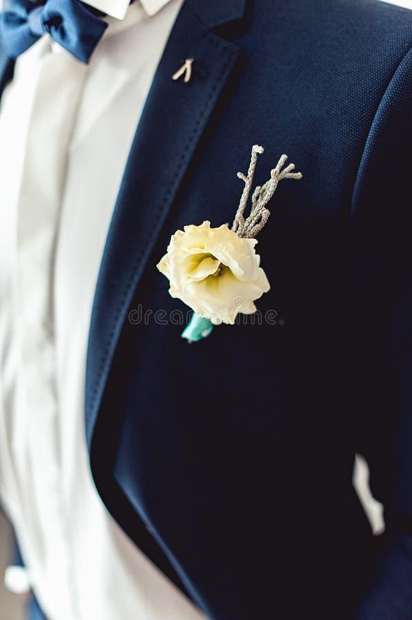 Details der männlichen Hochzeitskleidung Schöner Boutonniere festgesteckt auf Mann im blauen Anzug, im weißen Hemd und in der bla lizenzfreie stockbilder