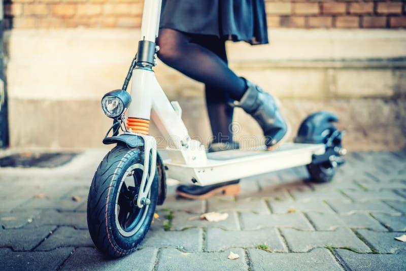 Details des modernen Transportes, elektrischer Trittroller, Porträt des Mädchens den Stadttransport reiten lizenzfreie stockfotos