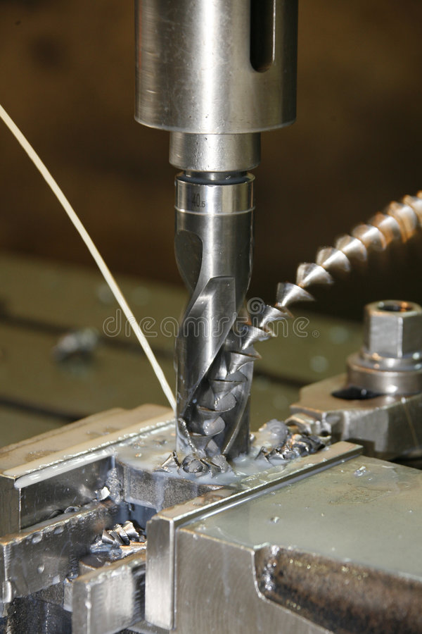 Details of drilling machine. A closeup view of a drill press as a steel bit drills into a piece of steel stock photography
