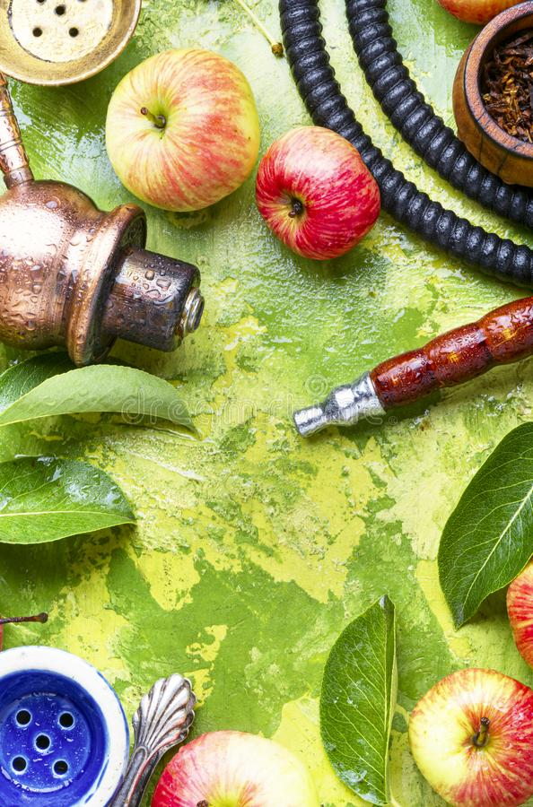 Smoking hookah with apple. Details of the eastern hookah.Hookah with apple flavor.Smoking apple tobacco stock photos