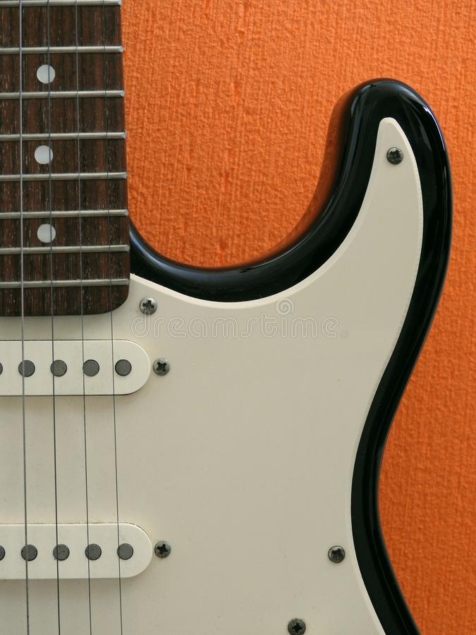 Details of a electric guitar: pickups, fingerboard and pickguard. Details of a electric guitar: we can see two pickups, part of the black body, the fingerboard stock photos