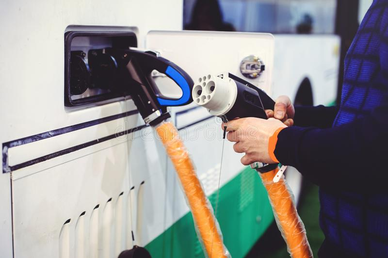 Details of electric vehicle charging city bus transport. Green and renewable energy sources. man holds in his hand.  stock photos