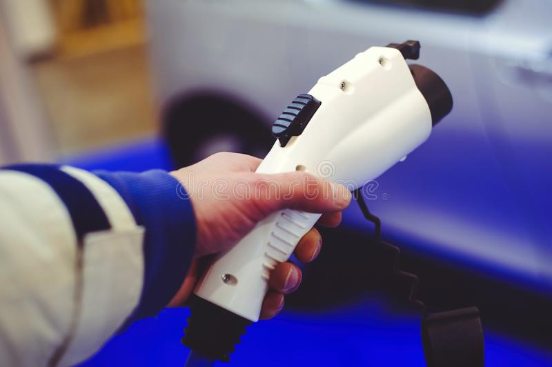 Details of electric vehicle charging. Green and renewable energy sources. man holds in his hand.  stock photo