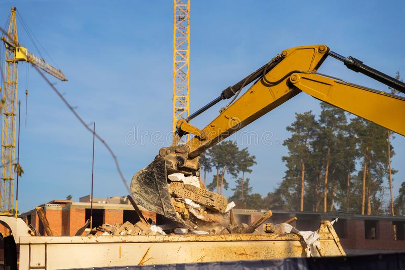 Details of excavator scoop destroying and loading debris into a dump truck. Construction background. stock images