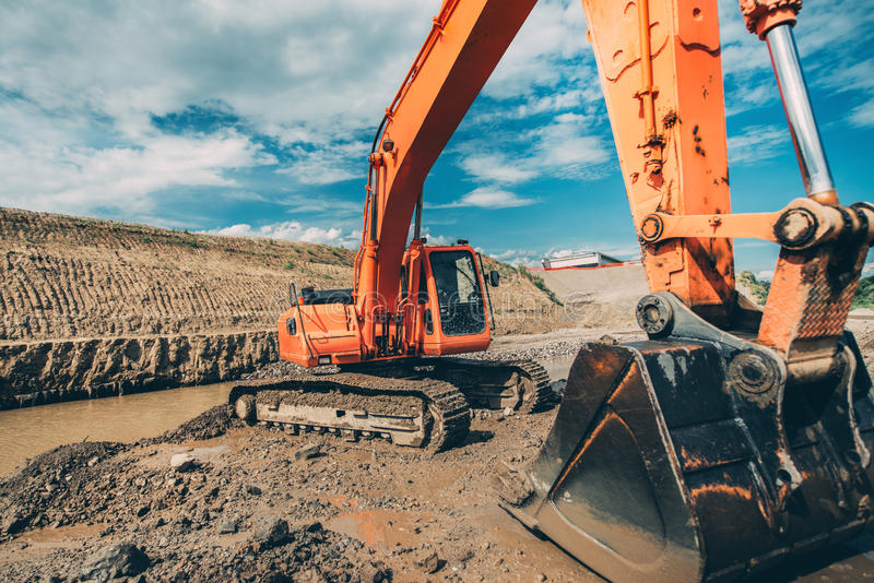 Details of excavator scoop during highway construction works. Industry with machinery. Close-up details of excavator scoop during highway construction works stock photo