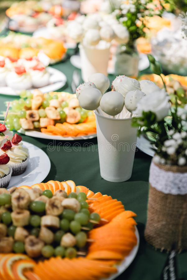Wedding catering. Outdoors fourchette. Details of a festival catering: fruits, cupcakes, macaroons and burgers. Sweet table at the feast. Delicious candy bar at stock photo