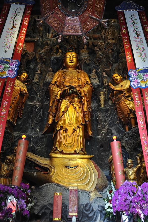 Golden Statue of Guanyin and Sudhana acompanied by their masters from the Jade Buddha Temple interior in Shanghai. Details from Golden Statue of Guanyin and stock photography