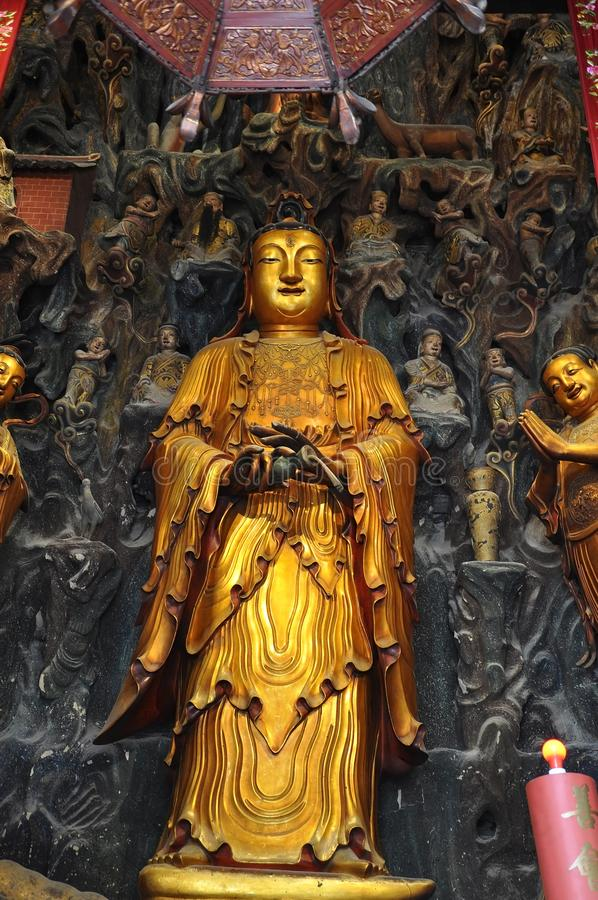 Golden Statue of Guanyin and Sudhana acompanied by their masters from the Jade Buddha Temple interior in Shanghai. Details from Golden Statue of Guanyin and stock photo