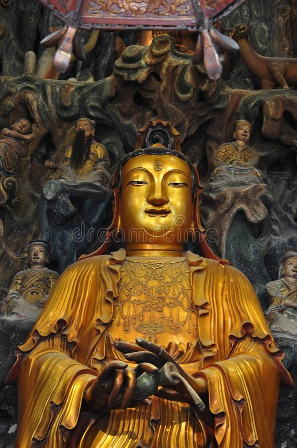Golden Statue of Guanyin and Sudhana acompanied by their masters from the Jade Buddha Temple interior in Shanghai. Details from Golden Statue of Guanyin and royalty free stock photo