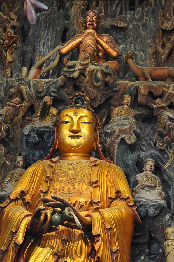 Golden Statue of Guanyin and Sudhana acompanied by their masters from the Jade Buddha Temple interior in Shanghai. Details from Golden Statue of Guanyin and royalty free stock photography