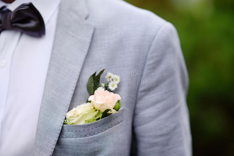Details of groom suit: boutonniere of fresh white rose and stylish bow tie royalty free stock photos