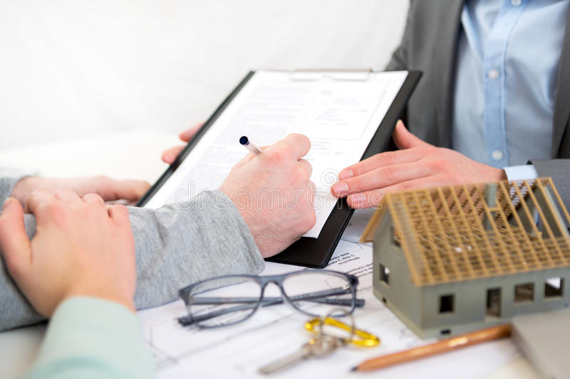 Details of hand signing contract at a real estate agent office royalty free stock image