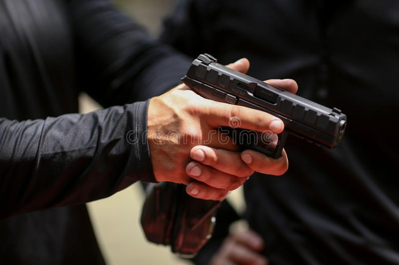 Details with the hands of a soldier handling a 9mm caliber Beretta PX4 Storm pistol stock image