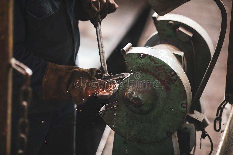 Details with the hands of a worker polishing a tool in a dirty and old but still functioning metal works, old fashioned, factory royalty free stock photo