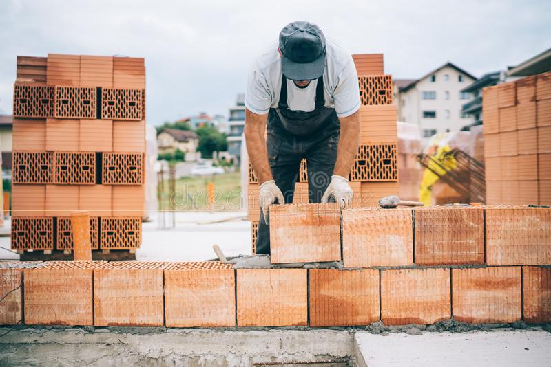 industrial bricklayer installing bricks on construction building site stock photography