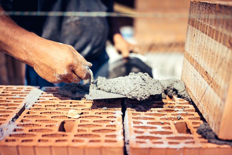 Details of industrial bricklayer installing bricks on construction site stock image