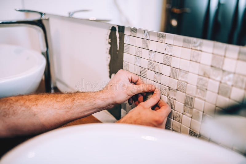 Details of industrial worker applying mosaic ceramic pattern tiles on bathroom shower area royalty free stock photography