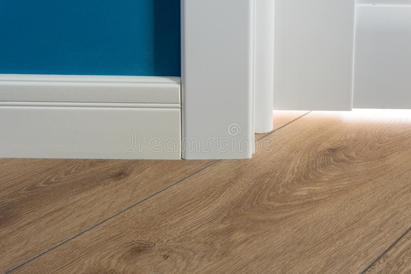 Details in the interior. Laminated parquet floors immitating oak texture, white baseboard, white door. Details in the interior. Laminated parquet floors royalty free stock photos