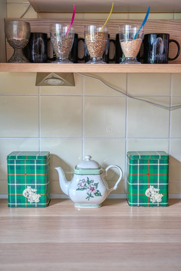 Details on a shelf in a kitchen with a teapot and mugs. Details on a kitchen shelf with a teapot, mugs and green checkered containers royalty free stock photo