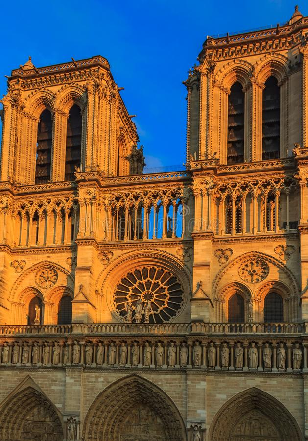 Details of the main facade of Notre Dame de Paris Cathedral facade with the oldest rose window and ornate tracery in the warm stock photography