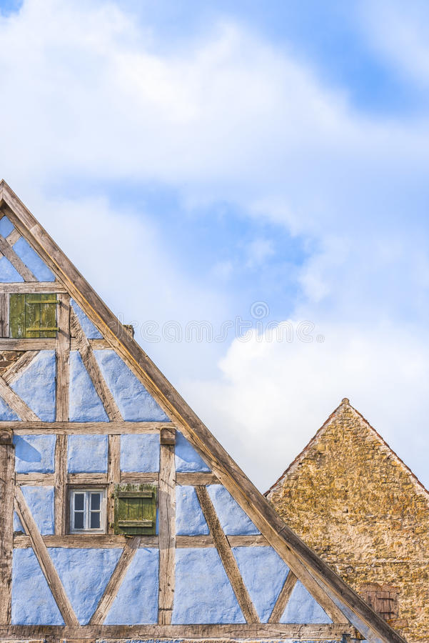 Details of medieval german gable roofs. Medieval architecture background with two german gable roofs, one house with blue half timbered walls and one with aged stock image