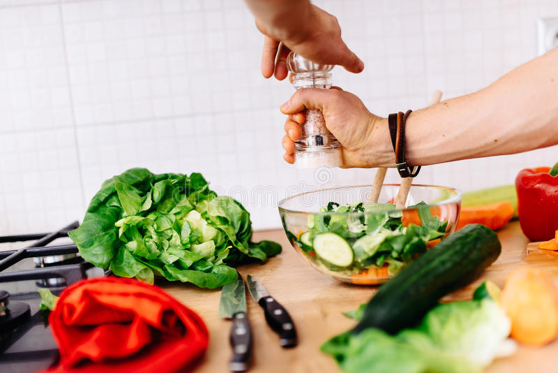 Details of mens hands adding salt and pepper to salad. perfect cook preparing salad for healthy life royalty free stock image