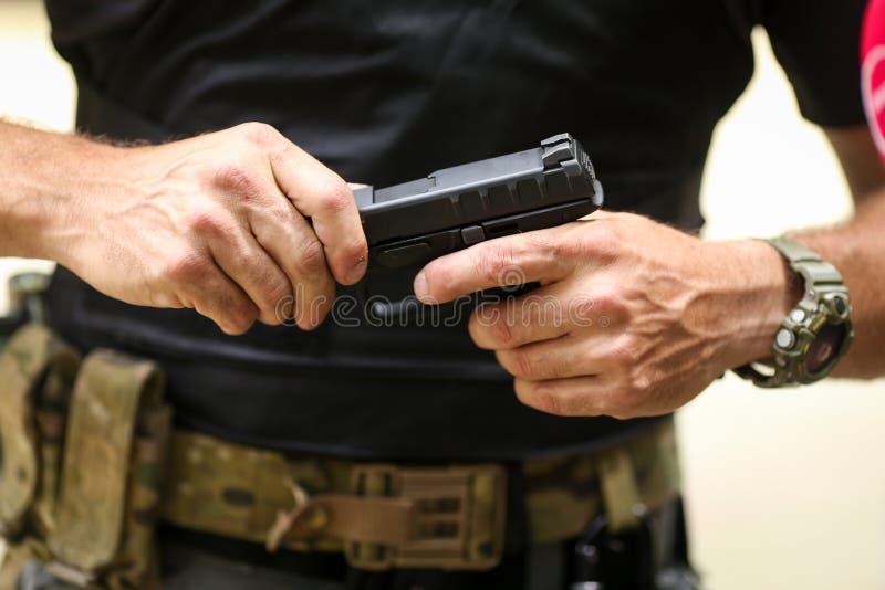 Details met de handen van een mens die een 9mm pistool behandelen stock foto's