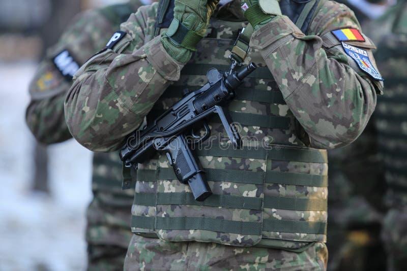 Details mit der Uniform eines rumänischen Militärpolizeisoldaten, bewaffnet mit einem Mikro-Uzi stockbild
