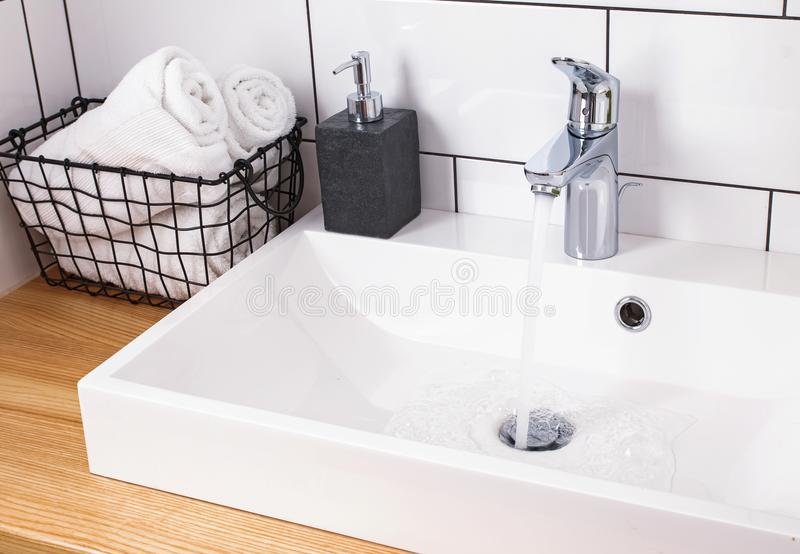 Details of modern bathroom with wite tile and wooden table stock image