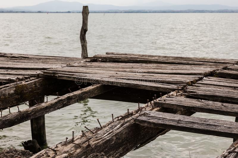 Details of an old, broken pier on a lake, with nails and worn and missing wood boards royalty free stock photo