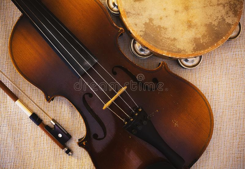Old Violin From Czechoslovakia and Tambourine. Details of an old and dusty violin from Czechoslovakia and tambourine royalty free stock image