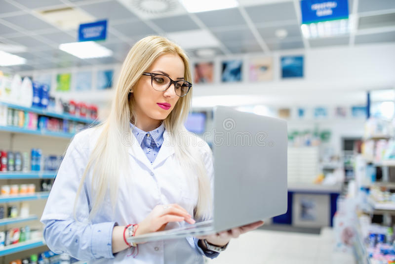 Details of pharmacy drugstore - blonde pharmacist searching for antibiotics on laptop. Pharmacy drugstore - blonde pharmacist searching for antibiotics on laptop stock photography