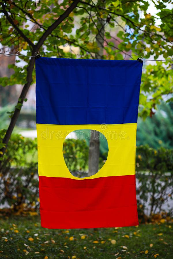 Details with the Romanian flag with a hole, the symbol of the Romanian Revolution from December 1989 when the communist emblem was royalty free stock photos