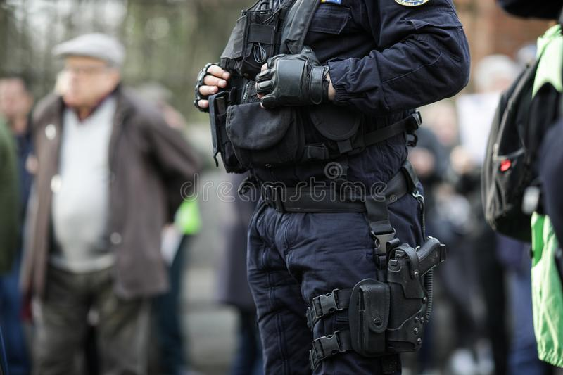 Details of the security kit of a riot police officer. Including handcuffs, 9mm handgun, radio station and baton sitting amongst civilians stock images