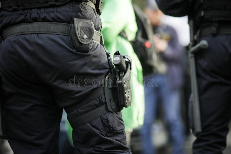 Details of the security kit of a riot police officer. Including handcuffs, 9mm handgun, radio station and baton sitting amongst civilians royalty free stock photo