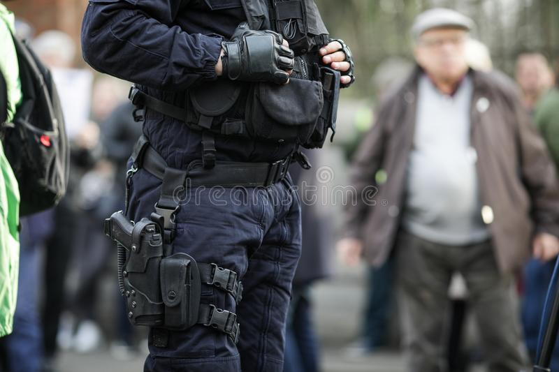 Details of the security kit of a riot police officer. Including handcuffs, 9mm handgun, radio station and baton sitting amongst civilians royalty free stock image