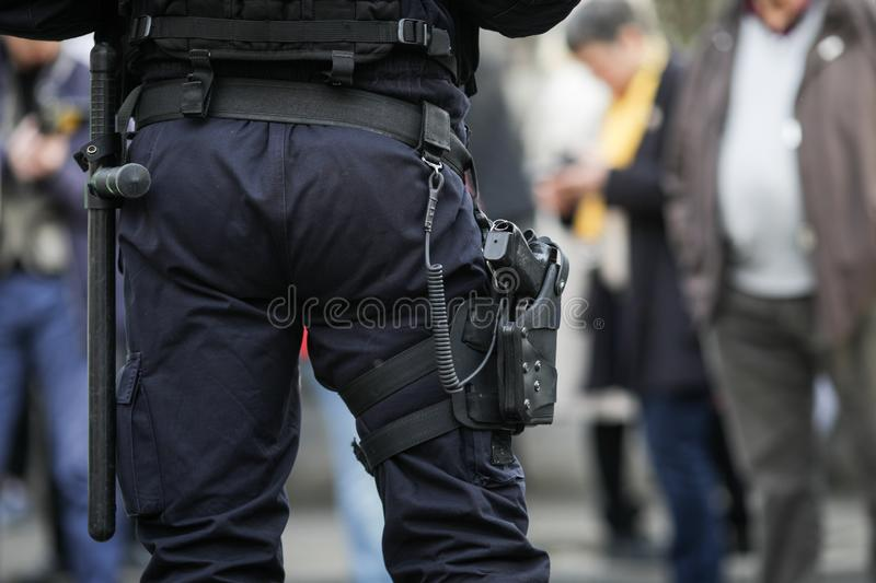 Details of the security kit of a riot police officer. Including handcuffs, 9mm handgun, radio station and baton sitting amongst civilians royalty free stock images