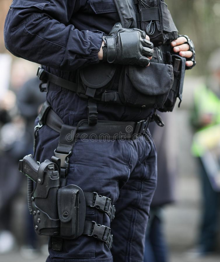 Details of the security kit of a riot police officer. Including handcuffs, 9mm handgun, radio station and baton sitting amongst civilians royalty free stock photos