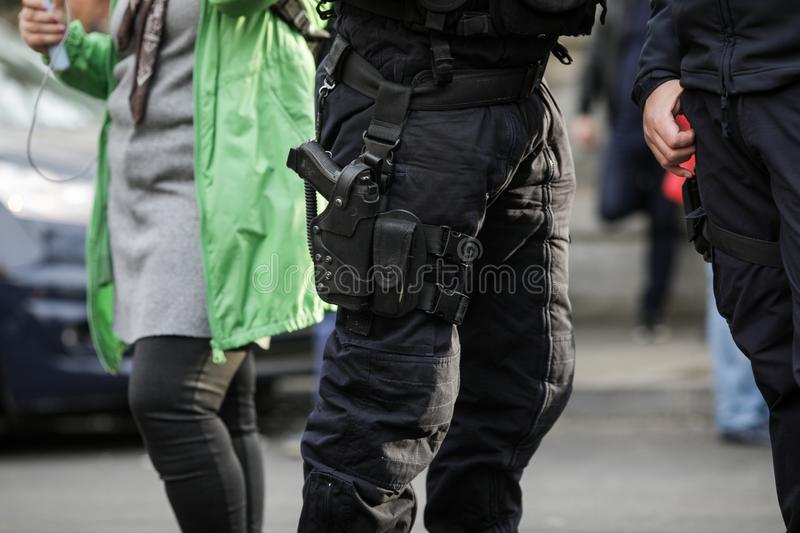 Details of the security kit of two riot police officers. Including handcuffs, 9mm handgun, radio station and baton sitting amongst civilians royalty free stock image