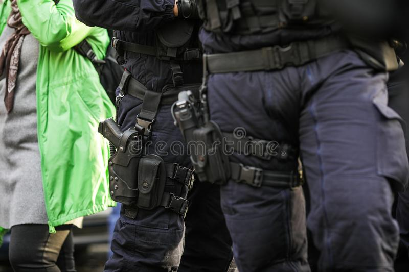 Details of the security kit of two riot police officers. Including handcuffs, 9mm handgun, radio station and baton sitting amongst civilians stock photos