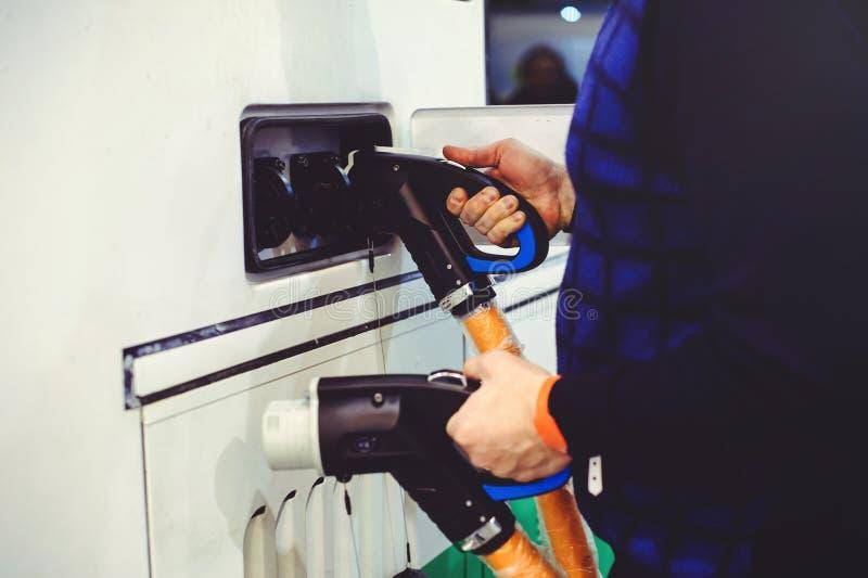 Details stadt-Bustransportes des Elektro-Mobils des Aufladungs Grün und erneuerbare Energiequellen Manngriffe in seiner Hand stockfotos