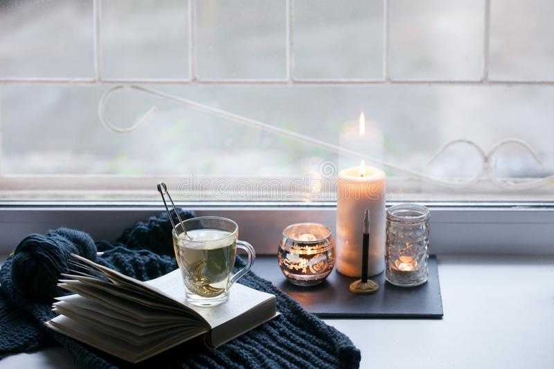 Details of still life in the home interior. Aroma stick, interior items, candles, Moody. Cosy autumn winter light concept. Copy. Space, monochrome background stock photography