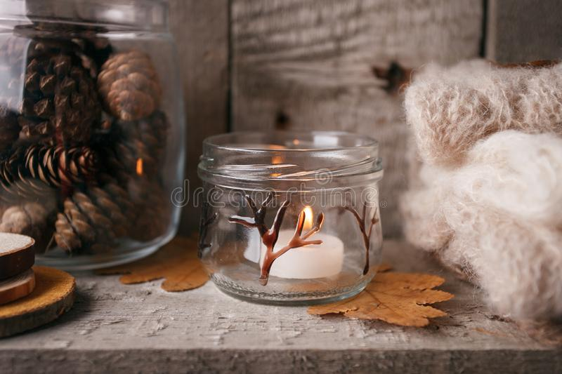 Details of still life in the home interior living room. Beautiful candlestick, cut wood, warm cloth, jar with pinecones, candle stock images