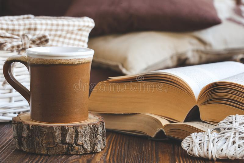 Details of still life in the home interior living room. Beautiful tea Cup, cut wood, books and pillows, candle on wooden backgroun royalty free stock images