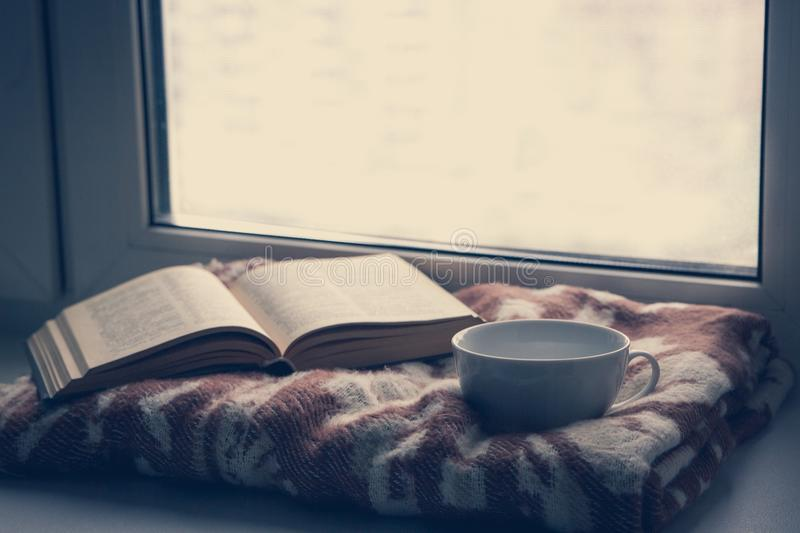 Details of still life in the home interior. Sweater, cup, wool, cozy, book, candle. Moody. Cosy autumn winter concept. royalty free stock images