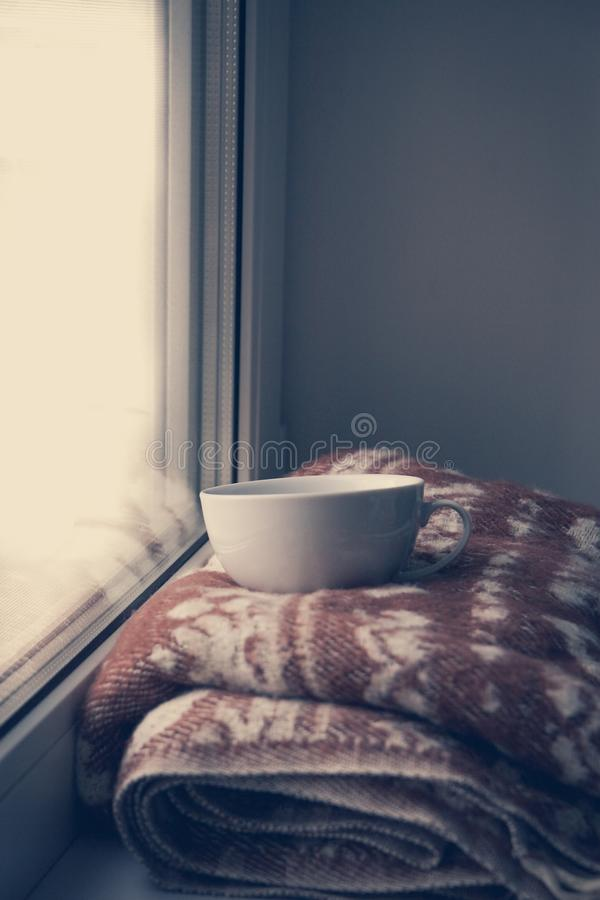 Details of still life in the home interior. Sweater, cup, wool, cozy, book, candle. Moody. Cosy autumn winter concept. Copy space royalty free stock images