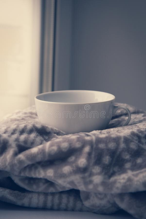 Details of still life in the home interior. Sweater, cup, wool, cozy, book, candle. Moody. Cosy autumn winter concept. Copy space stock image